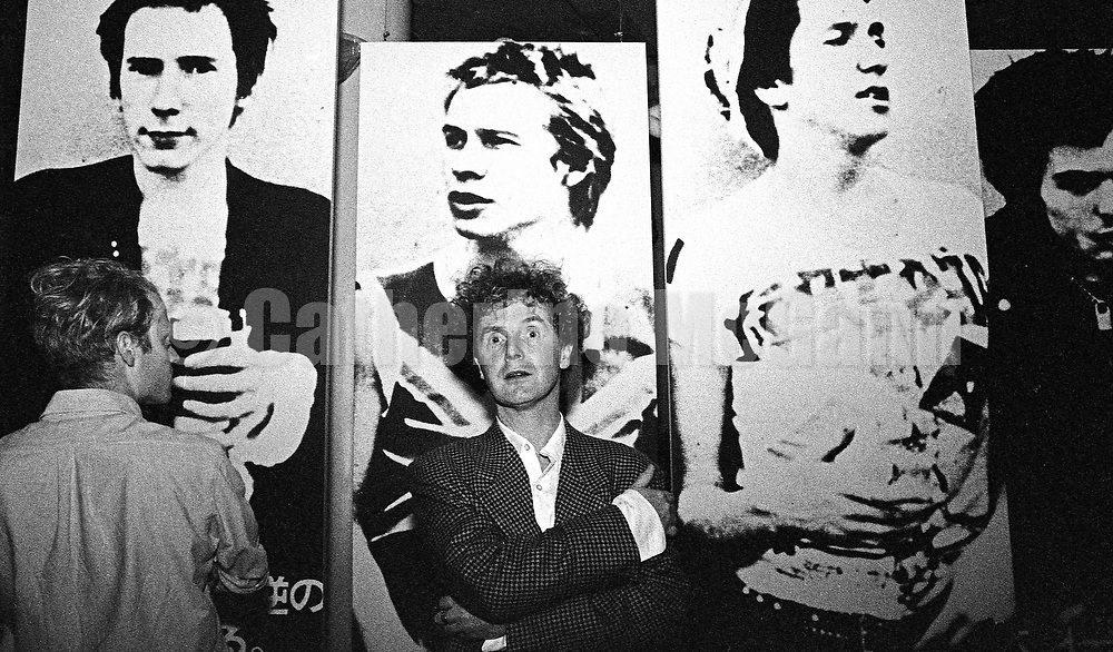 """September 14, 1988:  Malcolm McLaren (1946 2010) poses in front of blown up photos of the Sex Pistols at the opening reception of his exhibition at the New Museum of Contemporary Art in New York City, titled """"Impresario: Malcolm McLaren and the British New Wave""""."""