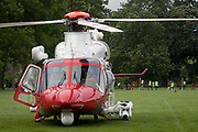 Local footballers play near an AgustaWestland AW139 helicopter operated by the UK Coastguard rescue which is briefly landed in Ruskin Park to deliver an emergency patient, on 8th June 2017, in the south London borough of Lambeth, England. The AW139 is used by Her Majesty's Coastguard (HMCG) which is a section of the Maritime and Coastguard Agency responsible for the initiation and co-ordination of all maritime search and rescue (SAR) within the UK Maritime Search and Rescue Region.