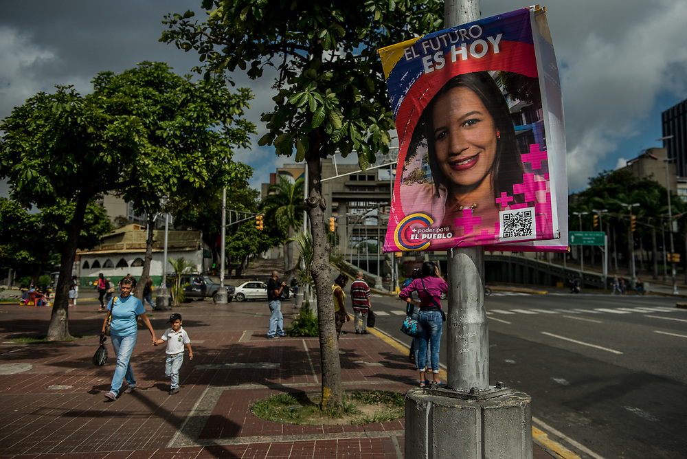 CARACAS, VENEZUELA - JULY 30, 2017:  People walk by a campaign poster for a candidate for the new National Constituent Assembly election. Many fear that today's election for a new National Constituent Assembly will turn Venezuela similar to Cuba. Lines to vote for the new National Constituent Assembly's candidates were significantly shorter across Caracas than those of the opposition's July 16th symbolic vote against the new assembly. Nonetheless, the government reported on state television that millions had turned out to vote. Opponents of the government criticize President Maduro for calling for this election - saying the new assembly is a power grab, and will be a puppet of the President - the only candidates on the ballot are government loyalists. Critics also fear the new assembly will turn the country into a dictatorship, re-write the constitution and wipe out the democratically elected and opposition controlled congress. There have been widespread reports of voter intimidation, and of the government threatening state workers and citizens that receive government benefits like subsidized food - who report the government telling them they are obligated to vote, and if they don't, they will lose their jobs and benefits. Thousands have taken to the streets to protest the election in the days leading up to the July 30th vote.  PHOTO: Meridith Kohut for The New York Times