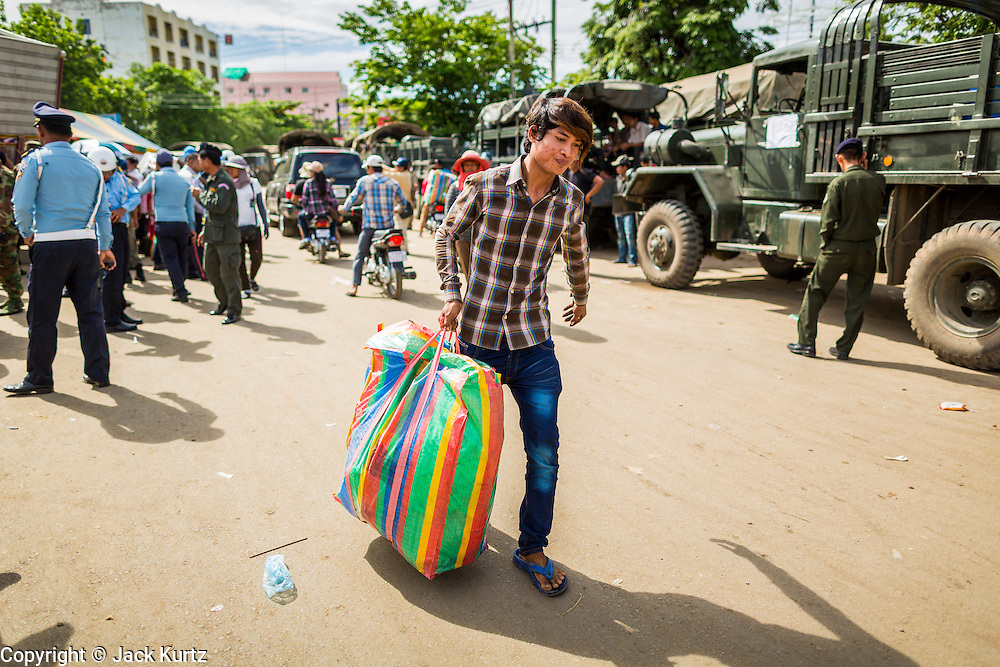 16 JUNE 2014 - POIPET, CAMBODIA: A Cambodian migrant carries his belongings through Poipet, Cambodia after he returned to Cambodia from Thailand. More than 150,000 Cambodian migrant workers and their families have left Thailand since June 12. The exodus started when rumors circulated in the Cambodian migrant community that the Thai junta was going to crack down on undocumented workers. About 40,000 Cambodians were expected to return to Cambodia today. The mass exodus has stressed resources on both sides of the Thai/Cambodian border. The Cambodian town of Poipet has been over run with returning migrants. On the Thai side, in Aranyaprathet, the bus and train station has been flooded with Cambodians taking all of their possessions back to Cambodia.  PHOTO BY JACK KURTZ