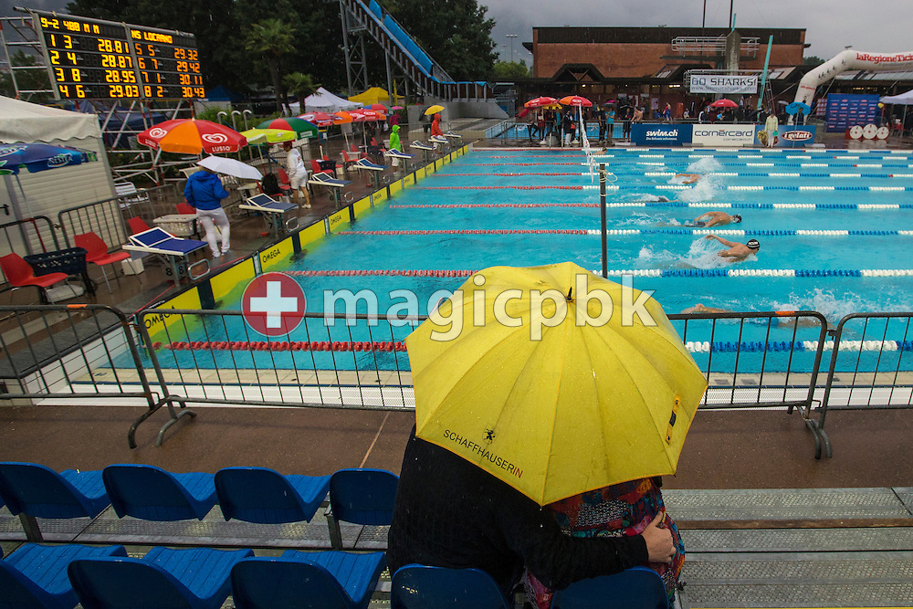 A couple under an umbrella is watching a race during the Swiss Swimming Summer Championships held at the 50m outdoor pool at the Centro sportivo nazionale della gioventu in Tenero, Switzerland, Friday, July 4, 2014. (Photo by Patrick B. Kraemer / MAGICPBK)