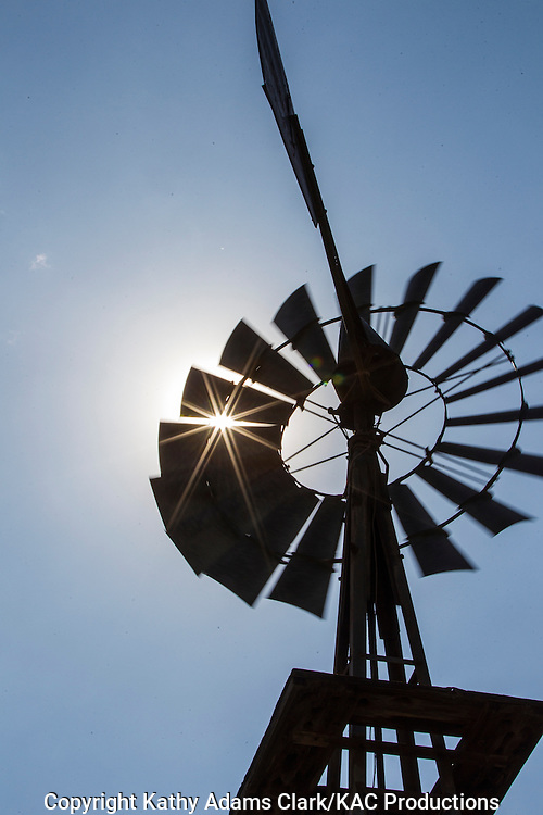 Sunburst or starburst from sun behind windmill at Dugout Wells in Big Bend National Park, Texas in late summer.