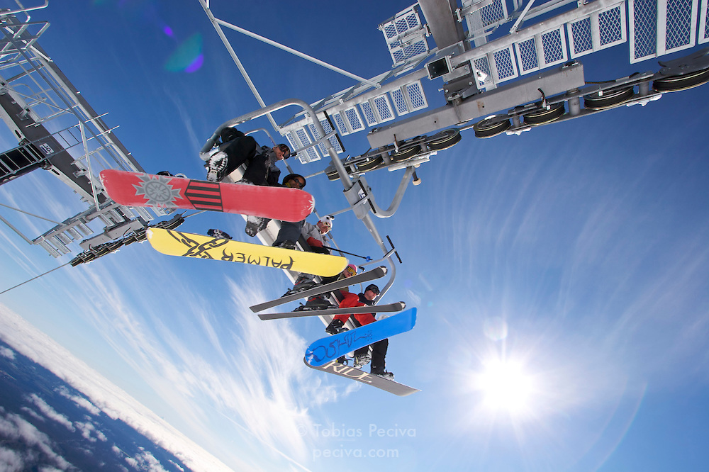 Four snowboarders and a skier going up a chairlift at ski field Turoa. Turoa is located on active volcano Mount Ruapehu, New Zealand.