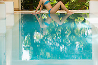 Young woman sitting by swimming pool side view low section