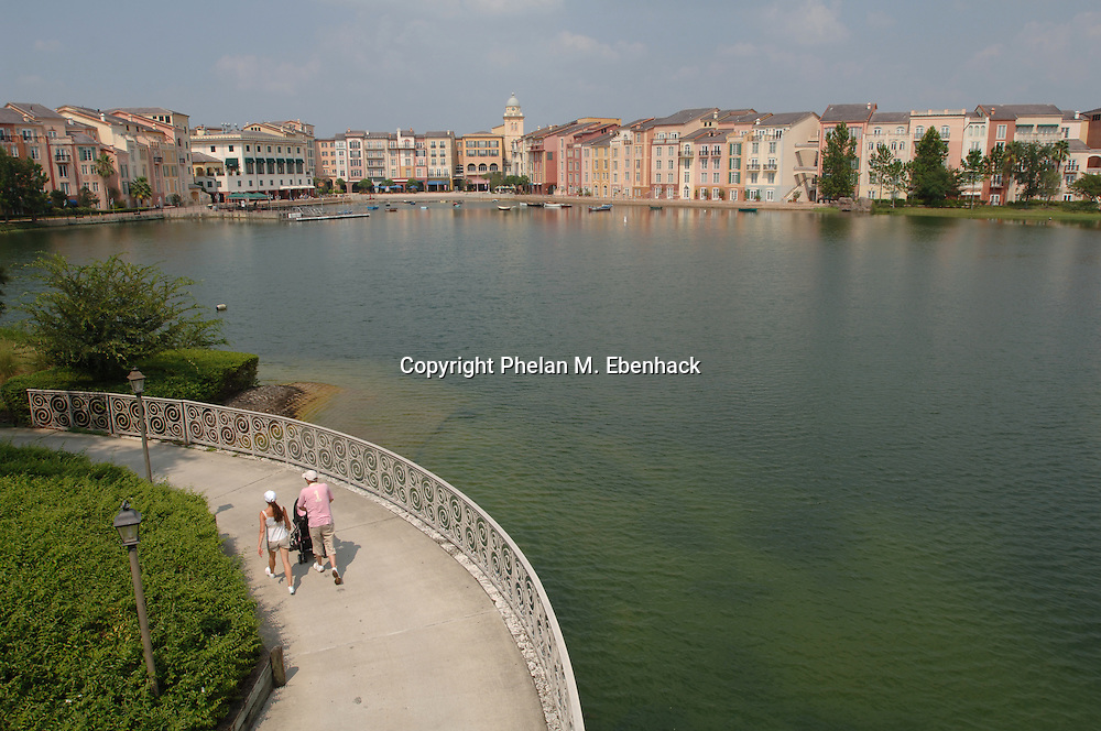 A family walks along a path from Universal Orlando CityWalk to the Portofino Bay Hotel at the Universal Orlando Resort in Orlando, Florida.