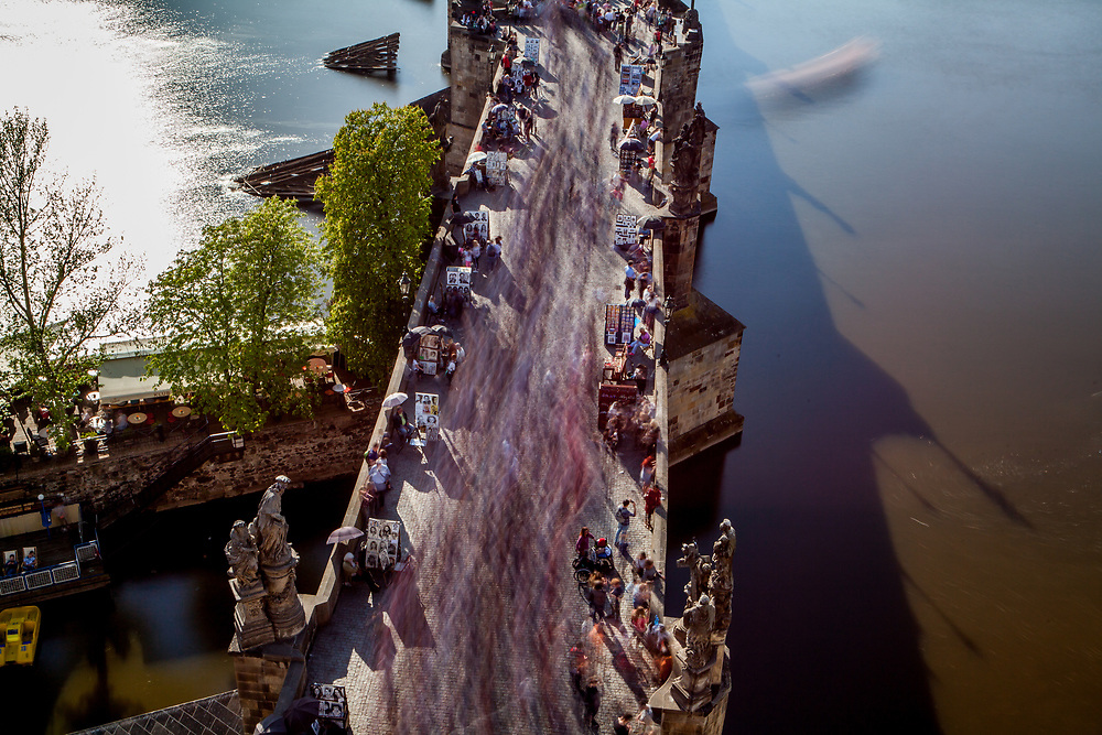 Crowds are moving across Charles Bridge seen from The Old Town Bridge Tower which is one of the most beautiful Gothic gateways in the world.