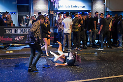 """© Licensed to London News Pictures . 24/12/2016 . Manchester , UK . A woman slips and falls in the road on Withy Grove . Revellers out in Manchester City Centre overnight during 2016's second """" Mad Friday """" , named for historically being one of the busiest nights of the year for the emergency services in the UK . Photo credit : Joel Goodman/LNP"""
