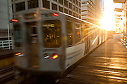"""A train in the Chicago rapid transit system known as the""""L"""" arrives in a station in the LOOP in Chicago, IL, USA."""