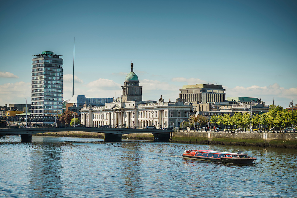 Dublin, Ireland, May 2013 : A tourist boat travels along the river liffey with the customs house and Liberty hall in the background