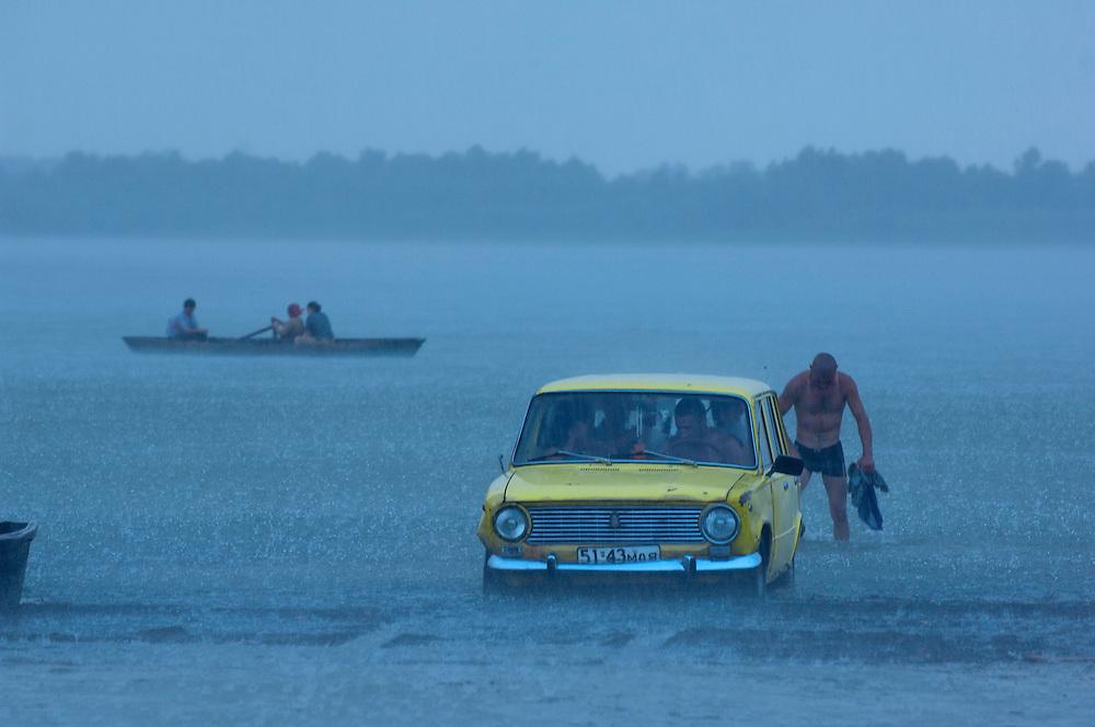 Fishermans car in water in rain, Lake Belau, Moldova, June 2009