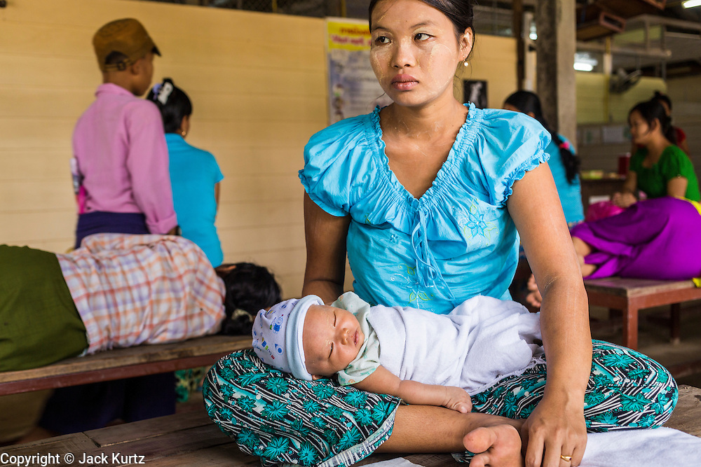 20 MAY 2013 - MAE KASA, TAK, THAILAND: A woman waits to see a medic during a routine exam for her and her newborn child in the SMRU clinic in Mae Kasa. Health professionals are seeing increasing evidence of malaria resistant to artemisinin coming out of the jungles of Southeast Asia. Artemisinin has been the first choice for battling malaria in Southeast Asia for 20 years. In recent years though,  health care workers in Cambodia and Myanmar (Burma) are seeing signs that the malaria parasite is becoming resistant to artemisinin. Scientists who study malaria are concerned that history could repeat itself because chloroquine, an effective malaria treatment until the 1990s, first lost its effectiveness in Cambodia and Burma before spreading to Africa, which led to a spike in deaths there. Doctors at the Shaklo Malaria Research Unit (SMRU), which studies malaria along the Thai Burma border, are worried that artemisinin resistance is growing at a rapid pace. Dr. Aung Pyae Phyo, a Burmese physician at a SMRU clinic just a few meters from the Burmese border, said that in 2009, 90 percent of patients were cured with artemisinin, but in 2010, it dropped to about 70 percent and is now between 55 and 60 percent. He said the concern is that as it becomes more difficult to clear the parasite from a patient, progress that has been made in combating malaria will be lost and the disease could make a comeback in Southeast Asia.    PHOTO BY JACK KURTZ