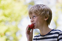 Boy (5-6) eating strawberry smiling