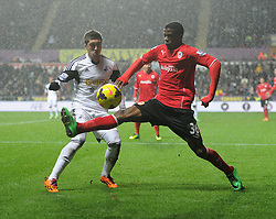 Cardiff City's Wilfred Zaha takes the ball from Swansea City's Leon Britton - Photo mandatory by-line: Alex James/JMP - Tel: Mobile: 07966 386802 08/02/2014 - SPORT - FOOTBALL - Swansea - Liberty Stadium - Swansea City v Cardiff City - Barclays Premier League