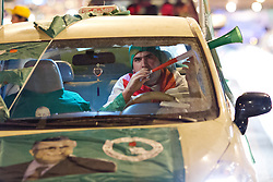 © Licensed to London News Pictures. 27/04/2014. Sulaimaniya, Iraq. Driving a car covered in Patriotic Union of Kurdistan (PUK) political party flags, A supporter blows a vuvuzela during celebrations in the lead up to the 2014 Iraqi parliamentary elections in Sulaimaniya, Iraqi-Kurdistan.<br /> <br /> Although banned in other parts of Iraqi-Kurdistan, the days leading up to an election in Sulaimaniya sees political supporters of all the three main parties parading up and down the main street of the city, waving flags, honking horns, letting off fireworks and firing pistols and rifles into the air.<br /> <br /> The period leading up to the elections, the fourth held since the 2003 coalition forces invasion, has already seen six polling stations in central Iraq hit by suicide bombers causing at least 27 deaths. Photo credit: Matt Cetti-Roberts/LNP