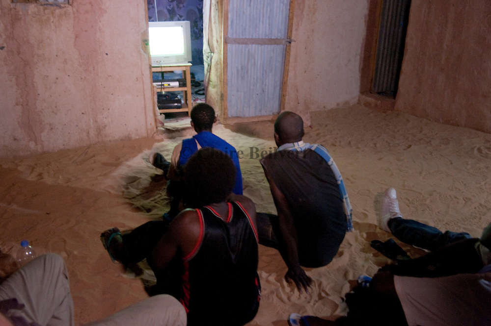 Young African migrants watching television in their ghetto in Dirkou, Niger