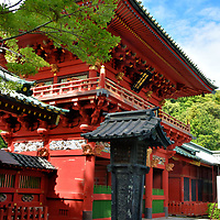 Rōmon at Shizuoka Sengen Jinja in Shizuoka, Japan<br /> At the main entrance of Shizuoka Sengen Jinja is this tower gate. The two-storied, wooden rōmon is painted in red lacquer and accented with gold leaf. After an extensive fire to the Sengen Jinja complex in 1804, the Tokugawa shogunate spent 60 years rebuilding the shrines. This gate was finished in 1815. In the foreground is a Japanese pedestal lantern called a tachidōrō. Notice the relief of the lion along the side.