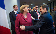 Nicolas Sarkozy, France's president, right, greets Angela Merkel, Germany's chancellor, as they move between their respective press briefings following the European Union Summit in Brussels, Belgium, on Friday, March 26, 2010. Sarkozy capped a week of reversals with his acceptance of German demands on a contingency plan to aid Greece. (Photo © Jock Fistick)