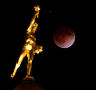Above the the Golden Boy, atop the Manitoba Legislative Building, a full moon becomes a blood moon as Canada experiences a full lunar eclipse, early Tuesday, April 15, 2014. (TREVOR HAGAN/WINNIPEG FREE PRESS)