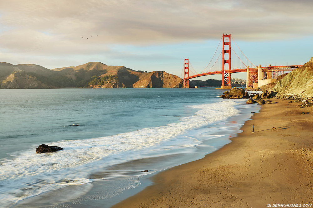 Scenic view of Golden Gate Bridge at sunset with a person standing Marshall's Beach in the foreground. San Francisco, California, USA