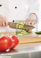 Salatgurke wird auf Schneidebrett geschnitten (model-released)