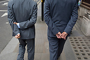 Two businessmen walk along a street, both with hands clasped behind their backs, in the City of London - the capital's financial district, on 4th June 2018, in London, England.