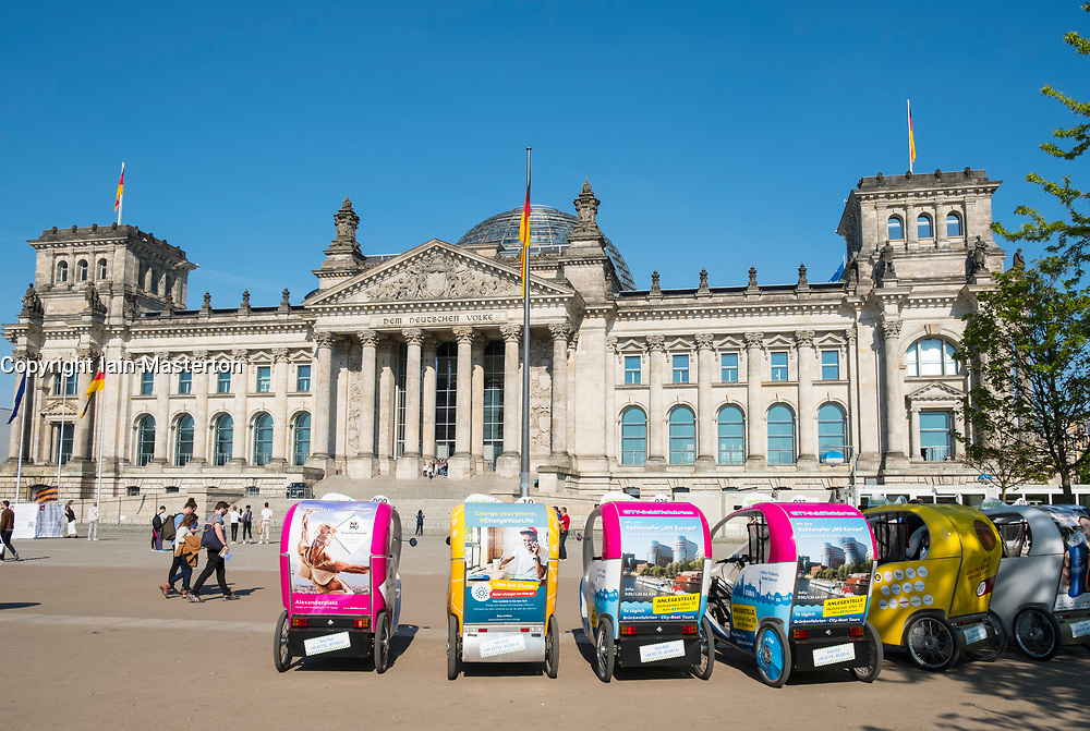View of Reichstag parliament building and tourist rickshaw bicycles in summer  in Berlin Germany