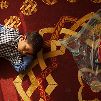 A child of the Al Shamaki family sleeps after the midday meal in the family's home in Sur, Oman.