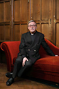 Patrick Chauvet, rector, seated on a red velvet chaise longue in a wood panelled room in the sacristy at the Cathedrale Notre-Dame de Paris, or Notre-Dame cathedral, built 1163-1345 in French Gothic style, on the Ile de la Cite in the 4th arrondissement of Paris, France. Patrick Chauvet is a prelate, preacher and catholic theologian, and has served as rector-archpriest at the cathedral since June 2016. In the sacristy, preparations are made for services and mass, and books and robes are stored. Photographed on 20th February 2019 by Manuel Cohen