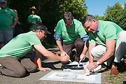 (L-R) Athens County Commisioner Chris Chmiel, City Planner Paul Logue, and Mayor Steve Patterson paint Mile Marker 0 on the HockHocking Adena bikeway. Mile Marker 0 is located near the Athens Community Center. © Ohio University / Photo by Kaitlin Owens
