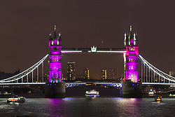 © Licensed to London News Pictures. 02/05/2015. London, UK. Tower Bridge in London is seen illuminated in pink as boats pass on the River Thames to celebrate the birth of a baby daughter to Catherine Duchess of Cambridge and Prince William today. Photo credit : Vickie Flores/LNP