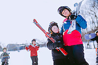 A family, Dad, mom, teenage girl, two boys, skiing and snowboarding at Wintergreen Resort in Virginia, in the the Blue Ridge Mountains. Skiing and snowboarding in Virginia. In the Blue Ridge mountains