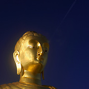 Face of Buddha with aeroplane in background