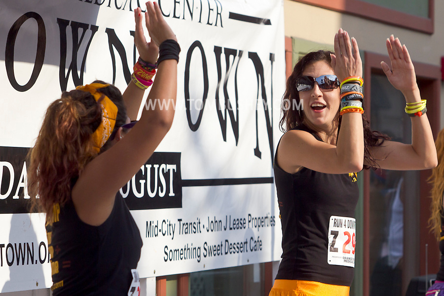 Middletown, New York - Instructors from Studio Ayo lead a Zumba in the Street warmup before the 2012 Run 4 Downtown road race on Saturday, Aug. 18, 2012.