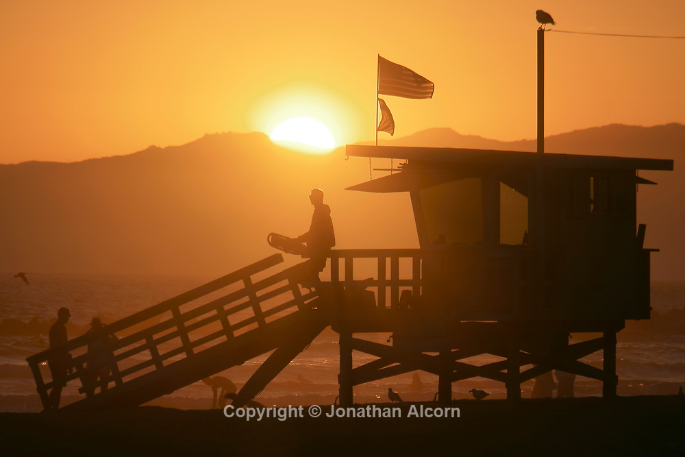 A lifeguard is pictured as the sun sets in Venice