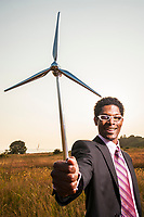 African American businessman holding a small wind turbine. Concept of wind power and green business.