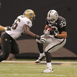 2008 October, 12: New Orleans Saints linebacker Jo-Lonn Dunbar (56) goes in for the tackle on Oakland Raiders returner Tyvon Branch (33) during a week six regular season game between the Oakland Raiders and the New Orleans Saints at the Louisiana Superdome in New Orleans, LA.