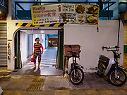 24 AUGUST 2018 - GEORGE TOWN, PENANG, MALAYSIA: A woman walks out of Chowrasta Market in central George Town. Chowrasta Market was originally built in 1890 and is the older of two traditional markets in George Town. The original building was torn down and replaced with a modern building in 1961 and has been renovated several times since.     PHOTO BY JACK KURTZ