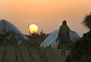 A Sudanese woman walks to fetch safe drinking water at sunset in the Kalma camp for internally displaced people (IDP) near Nyala, Southern Sudan Tuesday 12 October 2004. Water is a precious resource to the estimated 30 000 IDP's living in the Kalma camp. The violence in Sudan's Darfur region has driven more than 1.5 million people from their homes and created what the United Nations calls one of the world's worst humanitarian crises in the world today.<br /> EPA PHOTO/NIC BOTHMA