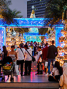 13 DECEMBER 2013 - BANGKOK, THAILAND: Tourists walk through the display of Christmas lights at Siam Paragon shopping center in the Ratchaprasong area of Bangkok. Thailand is overwhelmingly Buddhist. Christmas is not a legal holiday in Thailand, but Christmas has become an important commercial holiday in Thailand, especially in Bangkok and communities with a large expatriate population.      PHOTO BY JACK KURTZ