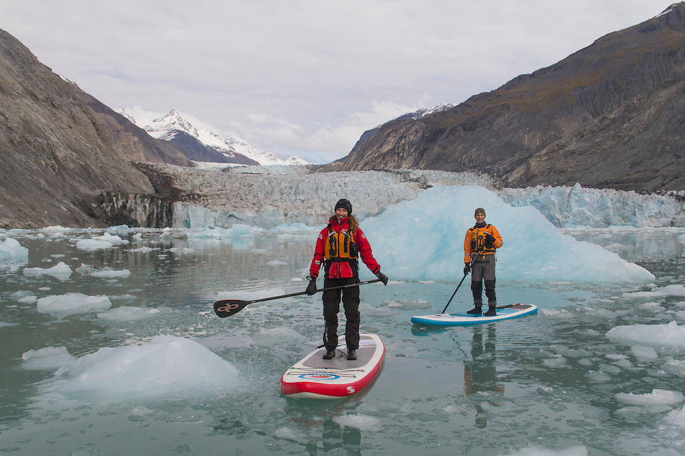 Stand up paddle boarders (SUP) paddle away from the face of McBride Glacier in Glacier Bay. MR
