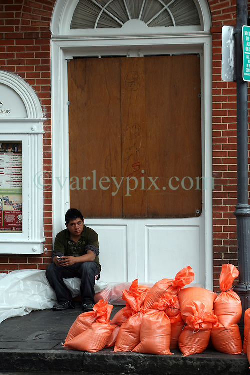 28 August 2012. New Orleans, Louisiana,  USA. <br /> A man sits behind sandbgs against a boarded up shop on an almost deserted Bourbon Street in the French Quarter. The 7th year anniversary of Hurricane Katrina is tomorrow and with a storm lurking in the Gulf many have evacuated as an uneasy calm settles over New Orleans.<br /> Photo; Charlie Varley