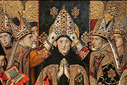 Consecration of St Augustin, or Consagracio de Sant Agusti, detail, c. 1462-75, tempera and stucco relief with gold leaf, from the St Augustine Altarpiece, by Jaume Huguet, 1412-92, in Gothic style, in the Museu Nacional d'Art de Catalunya, Barcelona, Spain. The painting depicts the saint being crowned by several bishops, in contemporary dress, with a donor reading on the left. This is a panel from the altarpiece from the convent church of Sant Agusti Vell, Barcelona, commissioned by the Guild of Tanners and painted by Jaume Huguet and Pau Vergos. The MNAC holds 7 of the 8 surviving panels from this altarpiece. Picture by Manuel Cohen