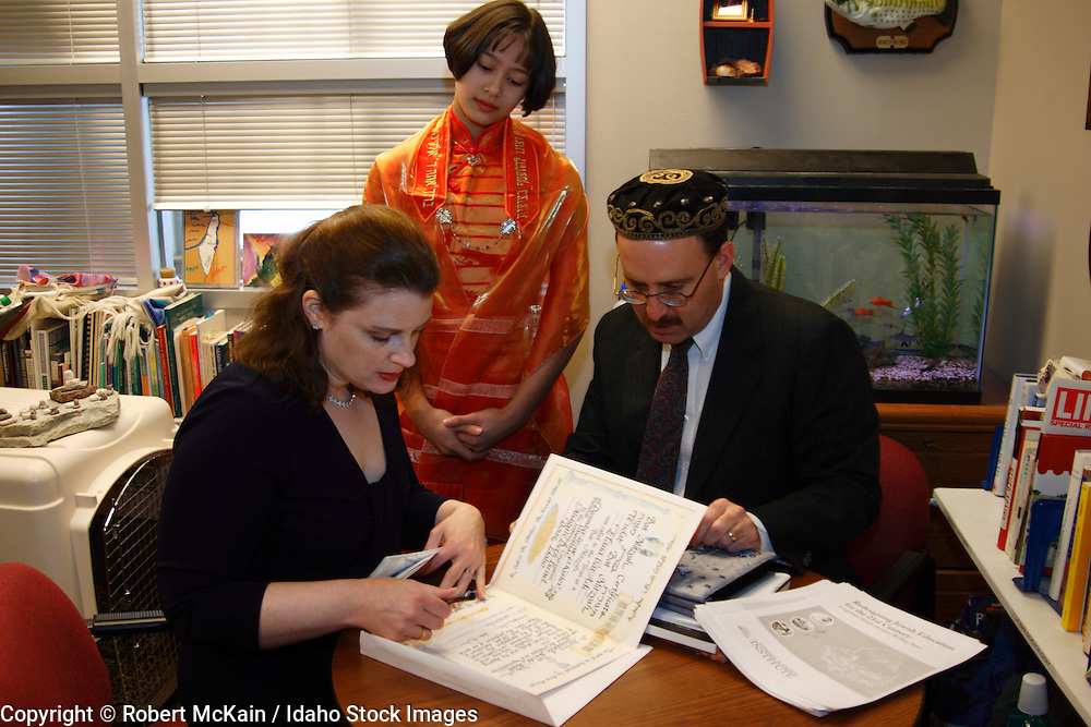 IDAHO. Boise. Rabbi with Asian Jewish girl and her mother signing her Bat Mitzvah certificate. December 2008. #pa080666 MR