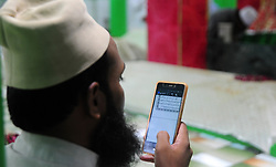 May 29, 2017 - Allahabad, Uttar Pradesh, India - Allahabad: A Muslim priest reads holy book the Quraan on his mobile before break his Ramadan fast at a mosque during Ramadan in Allahabad on 29-05-2017. Like millions of Muslim around the world, Indian Muslims celebrated the month of Ramadan by abstaining from eating, drinking, and smoking as well as sexual activities from dawn to dusk. (Credit Image: © Prabhat Kumar Verma/Pacific Press via ZUMA Wire)