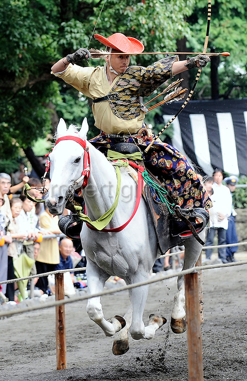 A horseback archer dressed in a traditional hunting garb aims an arrow at a target as his horse gallops along a 255-meter course at full pace during the Yabusame Shinji, a Japanese ritual, at Tsurugaoka Hachimangu shrine in Kamakura, near Tokyo on 17 Sept. 2008. The ritual, which dates back to the 12th century and is aimed at appeasing the numerous gods that guard Japan, was initiated by Kamakura shogun Minamoto no Yoritomo  in an attempt to improve his samurai warrior's appalling archery skills..Photographer: Robert GilhoolyA horseback archer dressed in traditional hunting garb is escorted along a 255-meter course during the Yabusame Shinji, a Japanese ritual, at Tsurugaoka Hachimangu shrine in Kamakura, near Tokyo. The ritual, which involves several riders on horseback firing arrows at targets while galloping at speed, dates back to the 12th century and is aimed at appeasing the numerous gods that guard Japan. It was initiated by Kamakura shogun Minamoto no Yoritomo in an attempt to improve his samurai warrior's appalling archery skills..Photographer: Robert Gilhooly