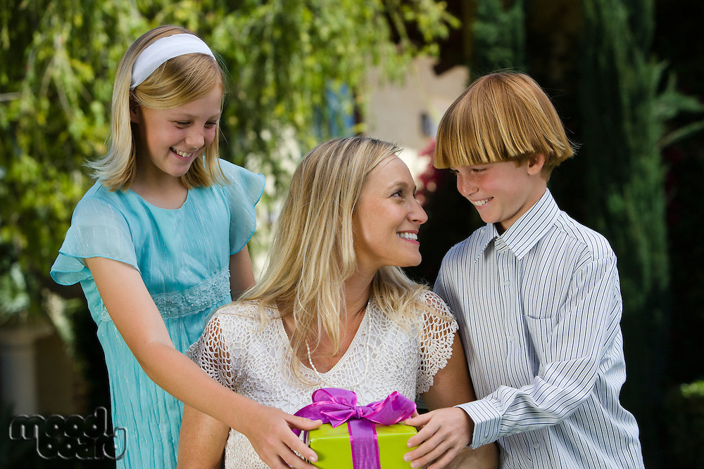 Mid-adult woman receiving birthday present from her son and daughter