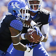 UK quarterback Jalen Whitlow hands off the ball to UK running back Jojo Kemp in the third quarter as the University of Kentucky plays the University of Louisville at Commonwealth Stadium in Lexington, Ky. Saturday Sept. 14, 2013. Louisville beat Kentucky 27-13. Photo by David Stephenson