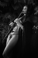 Sensual black and white portrait of a beautiful sexy Native American tribal woman playing a bamboo flute in the nature with her half nude body shining in dim light