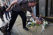 A londoner lays more flowers at the makeshift shrine, where Londoners commemorate Apple's creator Steve Jobs the morning after hearing of his death overnight from pancreatic cancer  at the age of 56 on the 6th Oct 2011. This Apple Store in the capital's Regent's Street was the first to be built in Europe and serves as a flagship outlet for the stylish brand of computer accessories that were largely the brainchild of Jobs who started the company as a student in 1977.