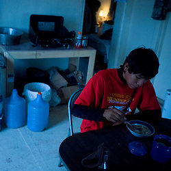 Yazzie Goodman eats breakfast in the dim morning glow of his home, which has no electricity.